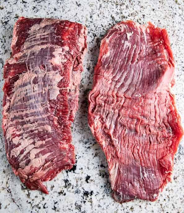 Side by side - Skirt steak and flank steak on a granite counter top