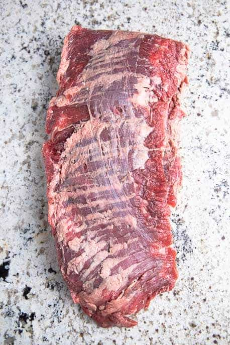 Raw skirt steak on a granite counter