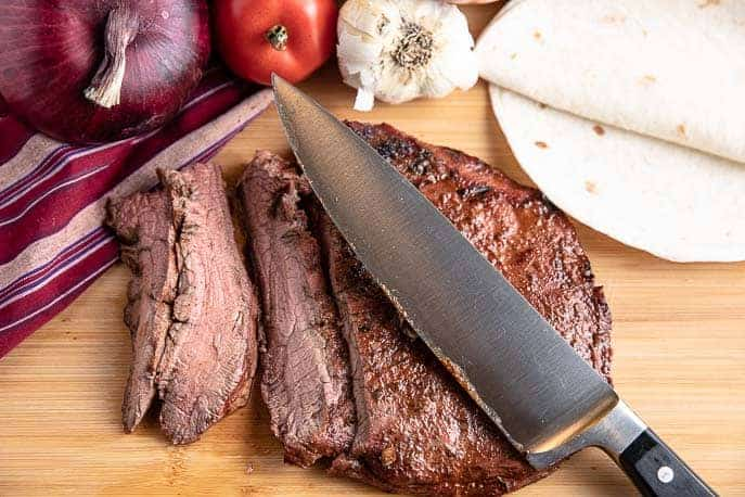 grilled flank steak on a cutting board with knife, onion, tomato, peppers, garlic and tortillas in background