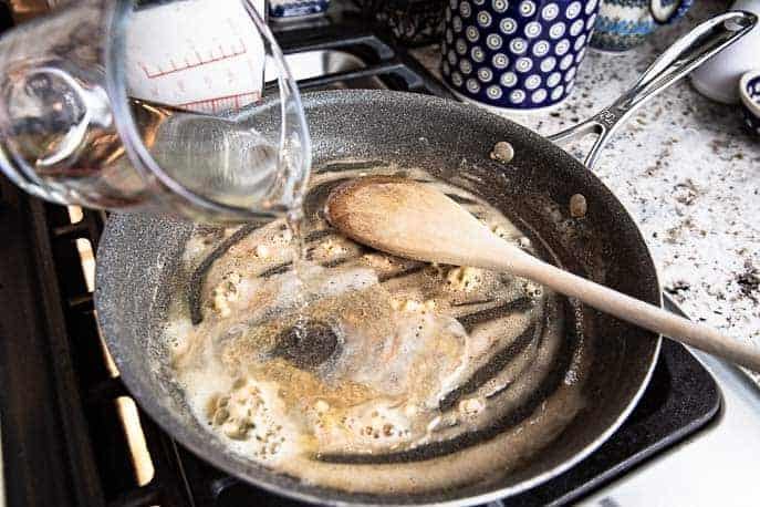 Wine being poured into skillet with melted butter and flour.