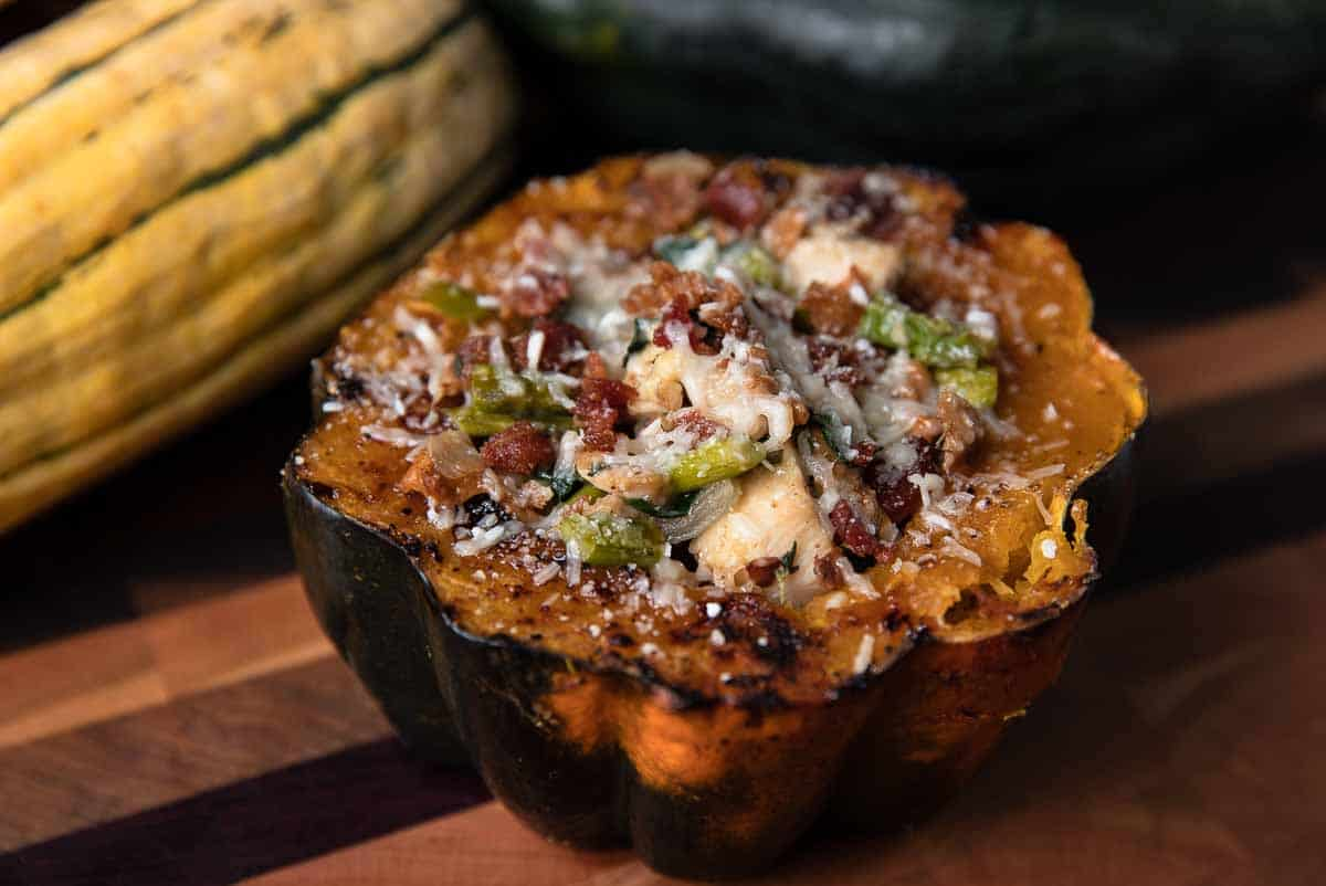 stuffed acorn squash on a wooden board with squash in the background