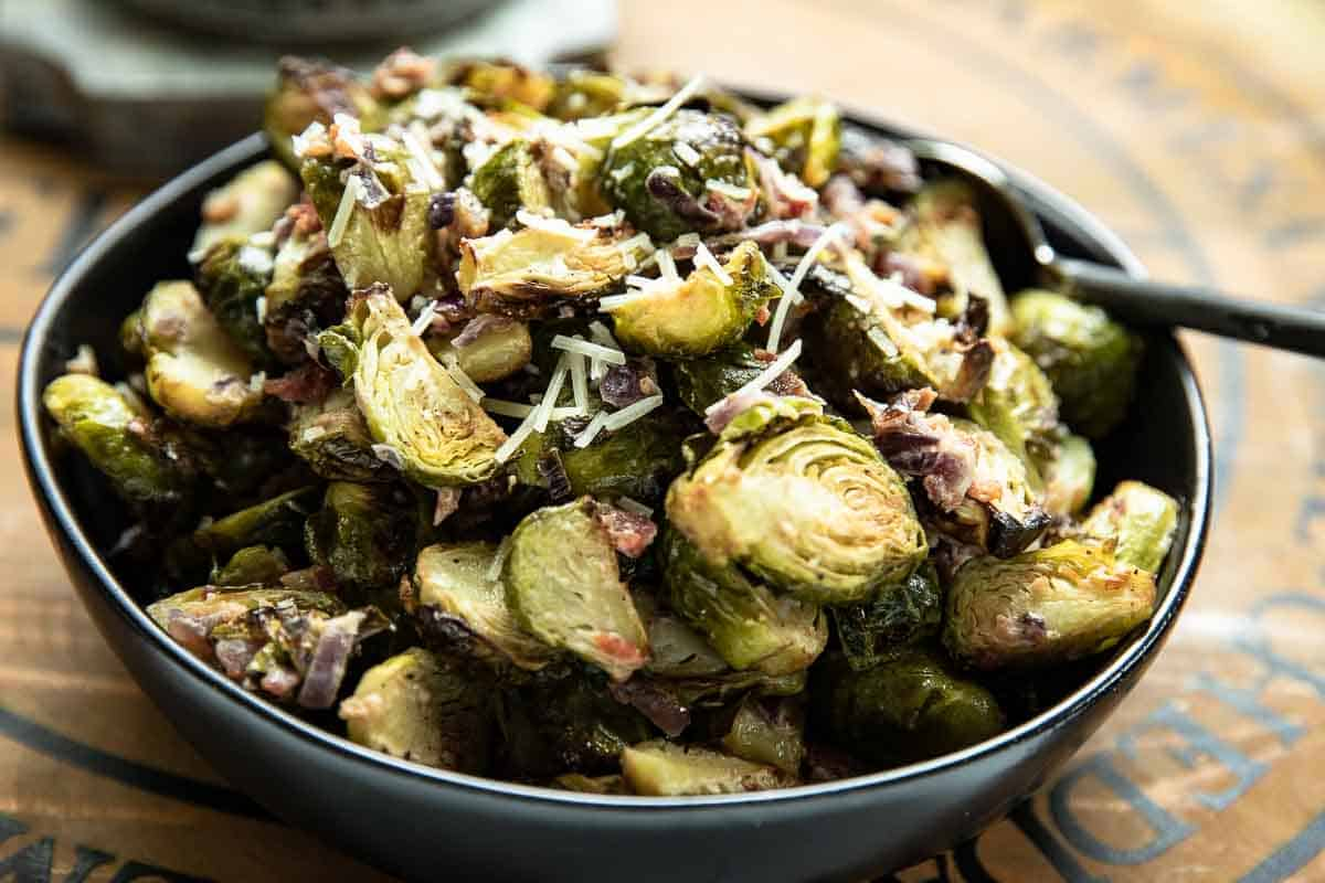 Roasted Brussels Sprouts in Creamy Parmesan Sauce in a black bowl on a wooden board with spoon