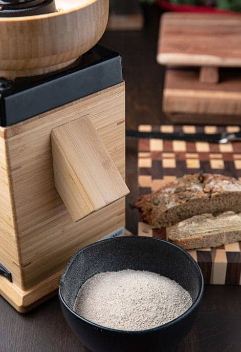 Flour grinder, board with sliced bread, black bowl with freshly ground flour