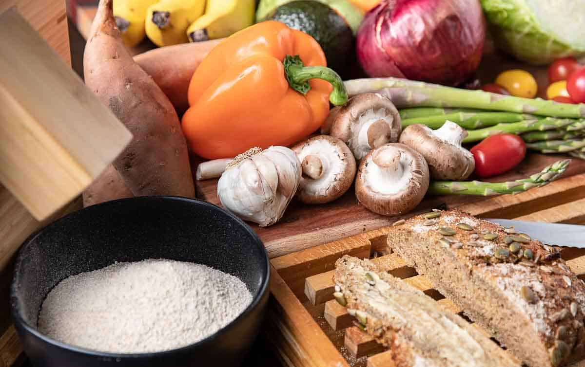 Fruits and vegetables, stone ground flour, fresh bread on a wooden board